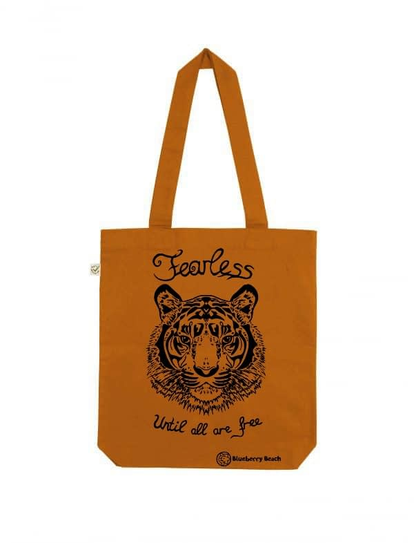 Organic tote bag with a tiger screen print and text fearless until all are free on it